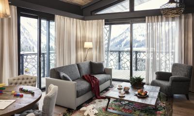 Gemütliches Wohnzimmer mit großem Balkon und Blick auf die Berge.