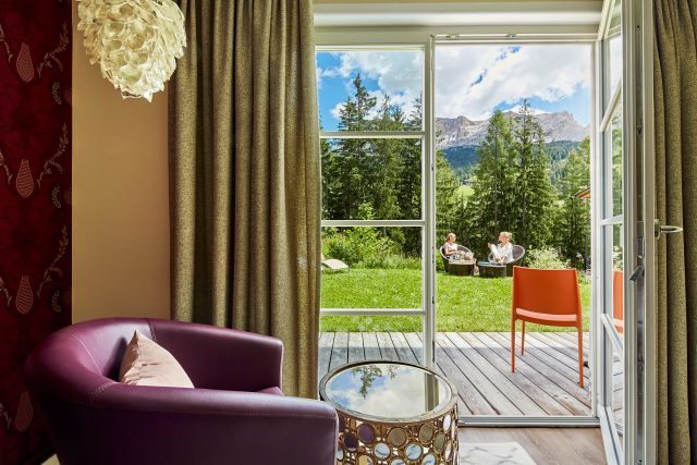 Wohnzimmer und Terrasse mit Ausblick auf die Dolomiten im Chalet Mi Amur. © Dolomit Homes